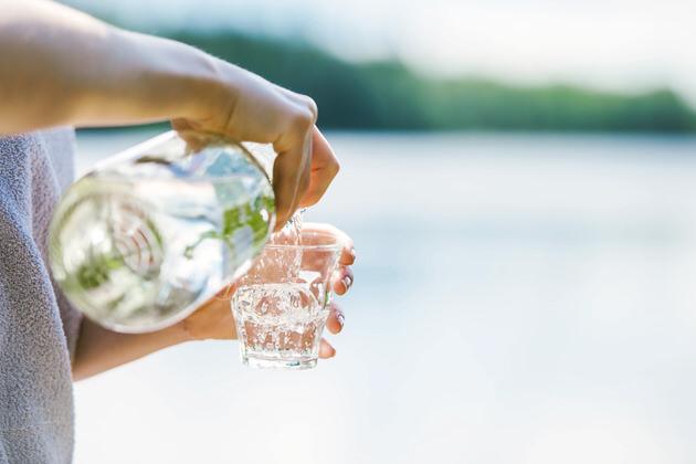 Nainen-kaataa-vetta-lasiin-laiturilla