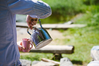 Pouring coffee into a cup by a campfire